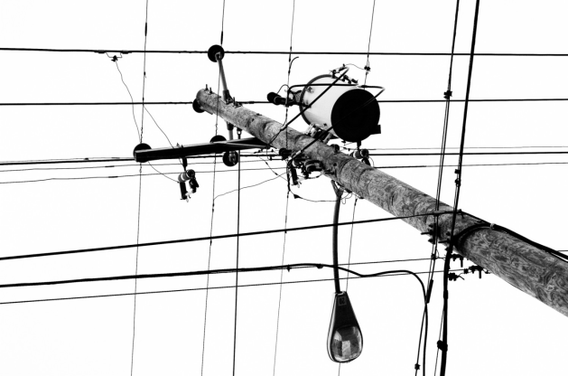 Black and white photograph of a telephone pole, with wires sticking out in a grid like pattern.